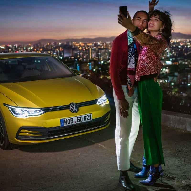 Ein Pärchen macht ein Selfie vor einem gelben VW Golf, im Hintergrund ein Tal mit einer Großstadt.