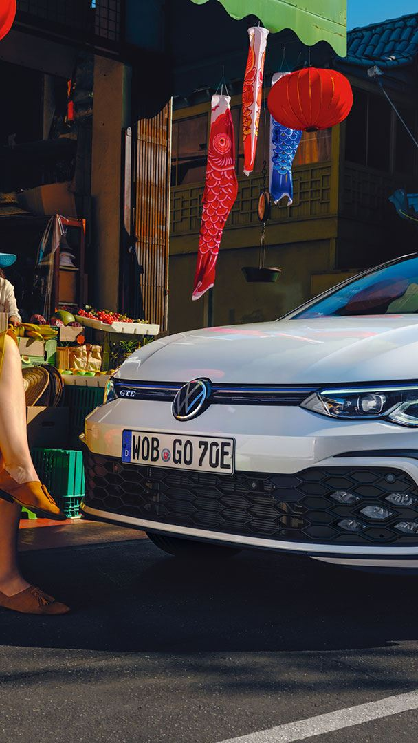 VW Golf GTE in white, front side view, stands on a street, 2 women are sitting in front of it