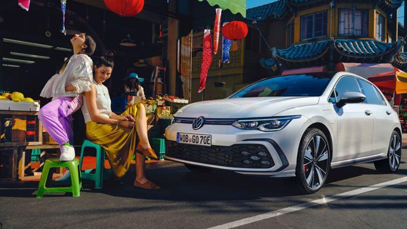 VW Golf GTE Seitenansicht steht auf einer Strasse, davor sitzen 2 Frauen