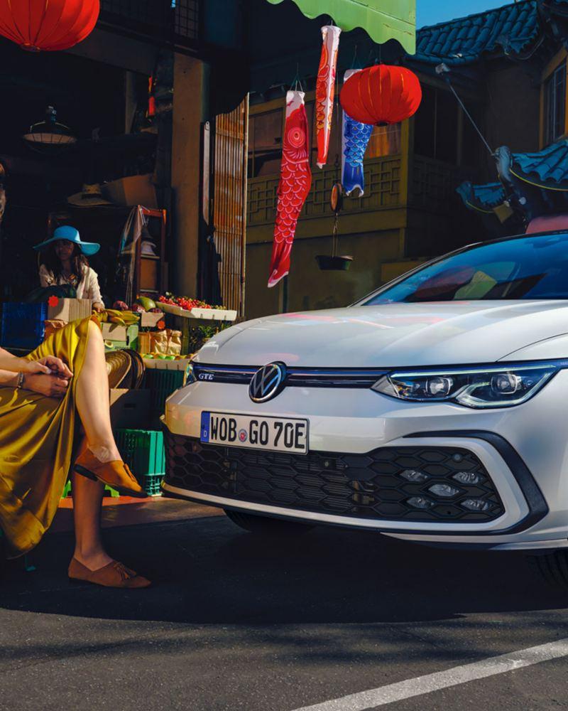 Ein weißer VW Golf GTE parkt am Straßenrand neben einem bunten Marktstand. 2 Frauen posieren davor.