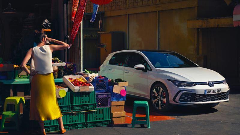 Ein weißer GTE parkt seitlich neben einem Obstand, davor kauft eine Frau ein und blickt zum E-Auto.