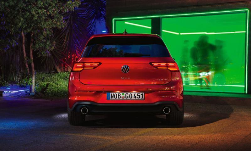 VW Golf GTI en rouge, vue arrière, garée devant un club