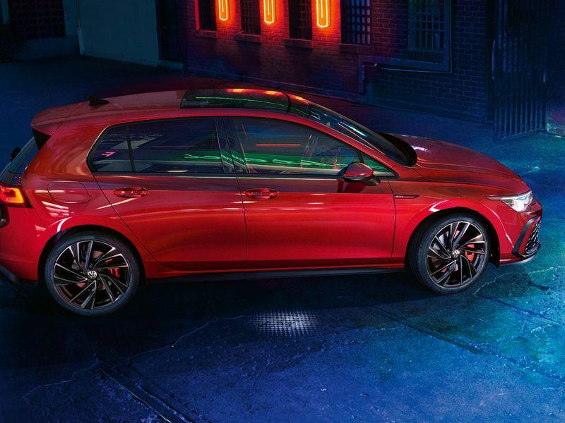 VW Golf GTI en rouge, vue de côté, garée dans un entrepôt