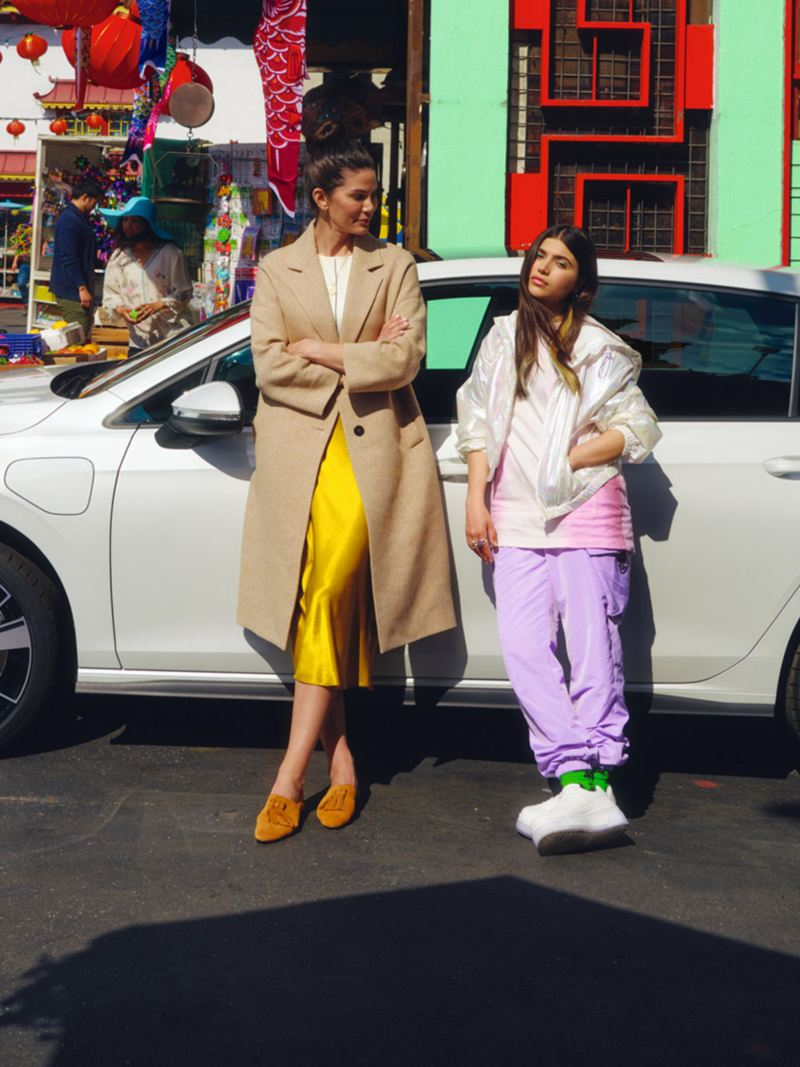 VW Golf GTE in white, side view, stands on a street in front of an Asian market, 2 women lean against it