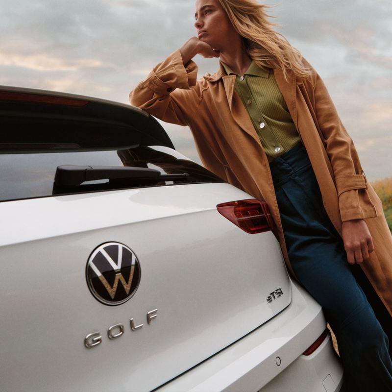 Una ragazza appoggiata alla sua Volkswagen Golf 8 eTSi, vista posteriormente con dettaglio sul badge.