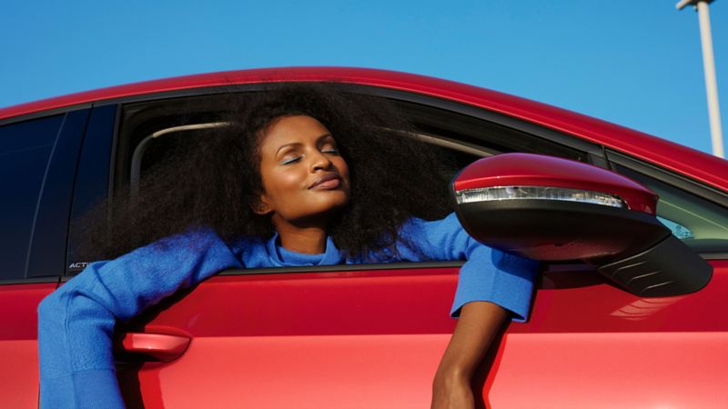 Une VW Golf rouge avec une fenêtre ouverte. Une femme en pull bleu se penche vers l'extérieur.