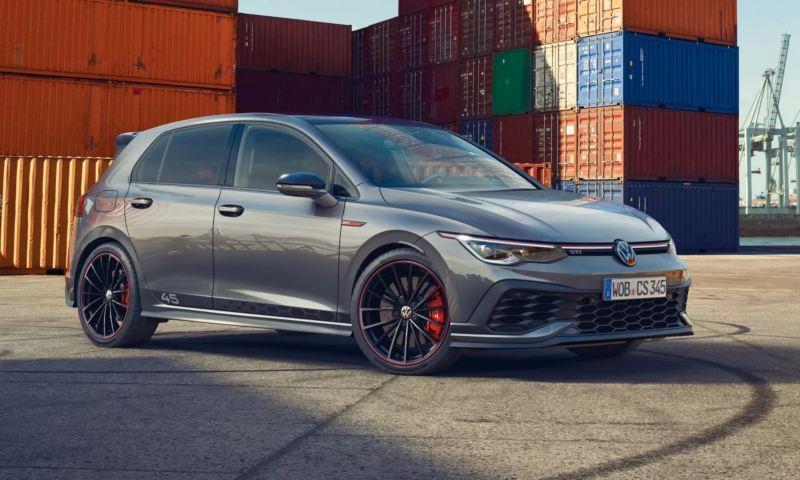 La VW Golf GTI Clubsport 45 grise se dresse au milieu de traces de pneus sur le sol, à côté d'un port. Ses étriers de freins rouges accrochent le regard.