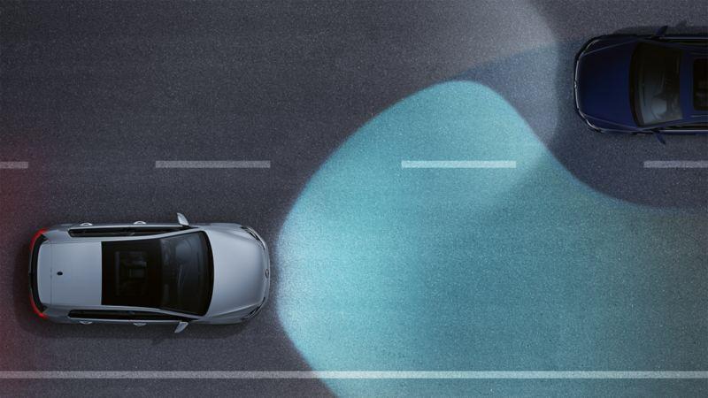 Volkswagen nocą na drodze widziany z góry. Widać regulację świateł drogowych jako stożek światła.