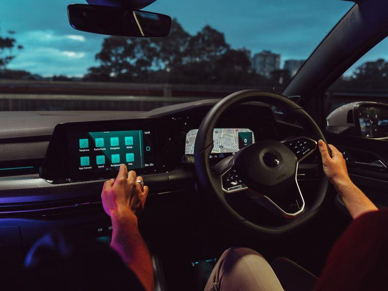 Wide image of Volkswagen Golf interior in the dark, lit by neon lights and ambient lighting.