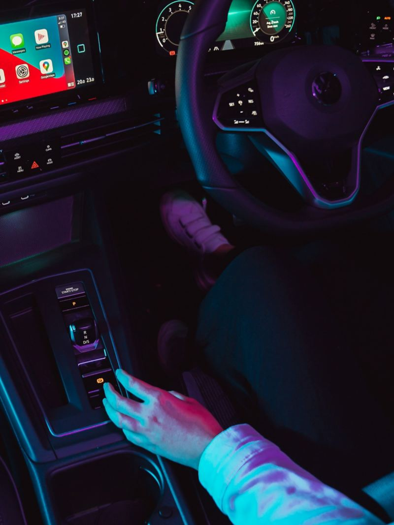 Close up of driver pushing automatic shifter in Volkswagen Golf.