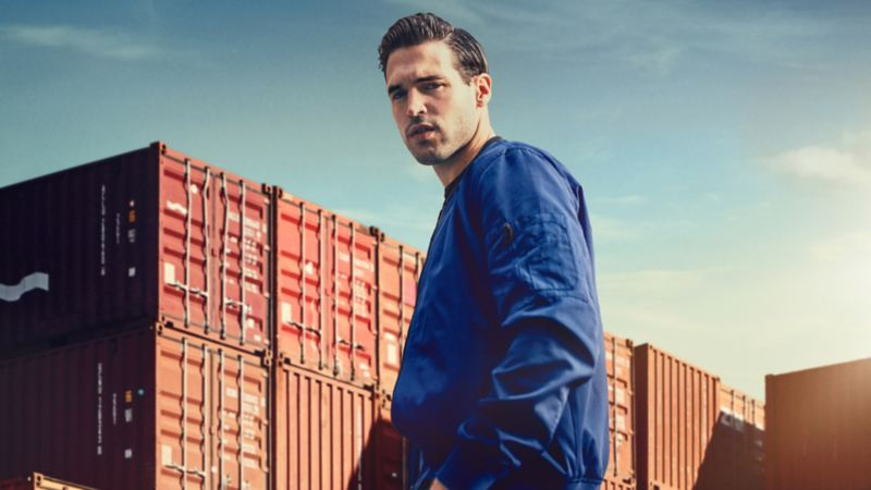Man in a blue jacket in front of cargo containers