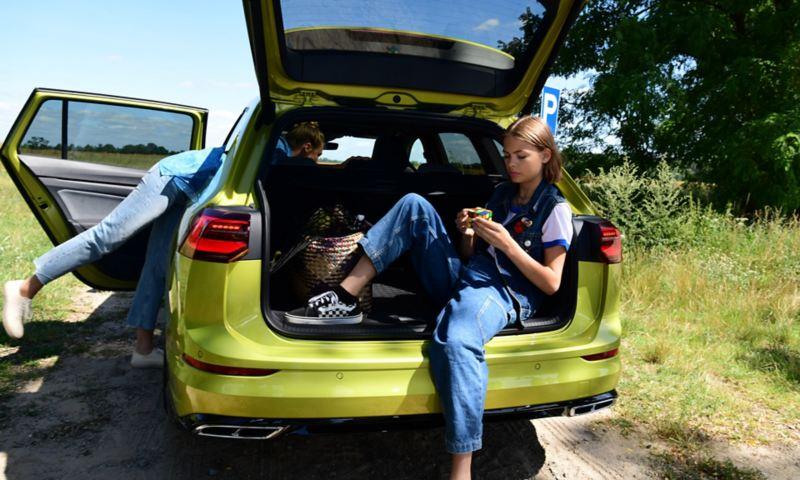 Una ragazza seduta nel bagagliaio aperto di una Golf Variant VW