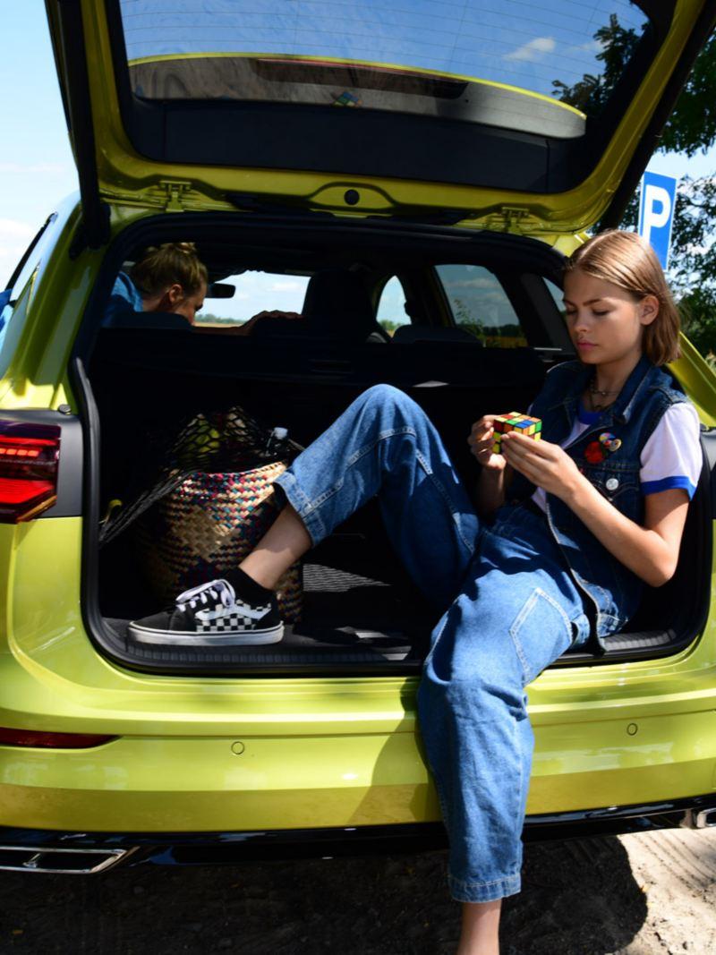 Une fille est assise dans le coffre ouvert d'une Golf Variant