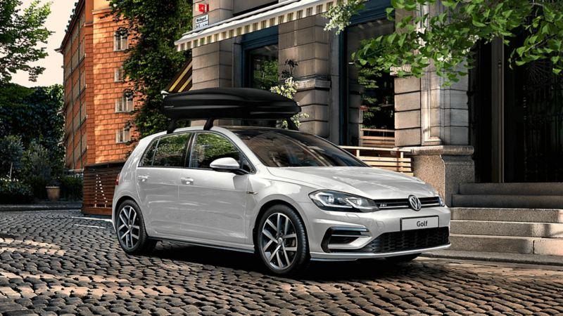 """Vista laterale di Volkswagen Golf 7 parcheggiata davanti ad un ingresso. Sul tettuccio il box da viaggio """"Comfort"""" originale Volkswagen."""