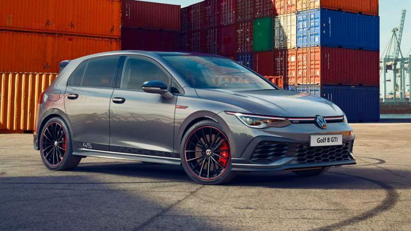 """Vista 3/4 frontale di Volkswagen Golf 8 GTI Clubsport 45 parcheggiata in prossimità di alcuni container. Si notano le pinze dei freni rosse che spiccano tra i cerchi in lega da 19""""."""