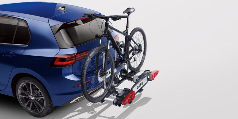 """Dettaglio del porta biciclette pieghevole """"Compact"""" originale Volkswagen, montato sul retro di una Golf 8. Disponibile per due o tre biciclette."""
