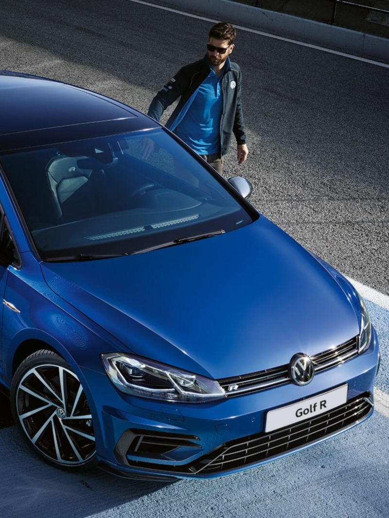 Top view of a Volkswagen Golf R MK7 painted in Lapis Blue Metallic parked on a racetrack, the driver standing next to it