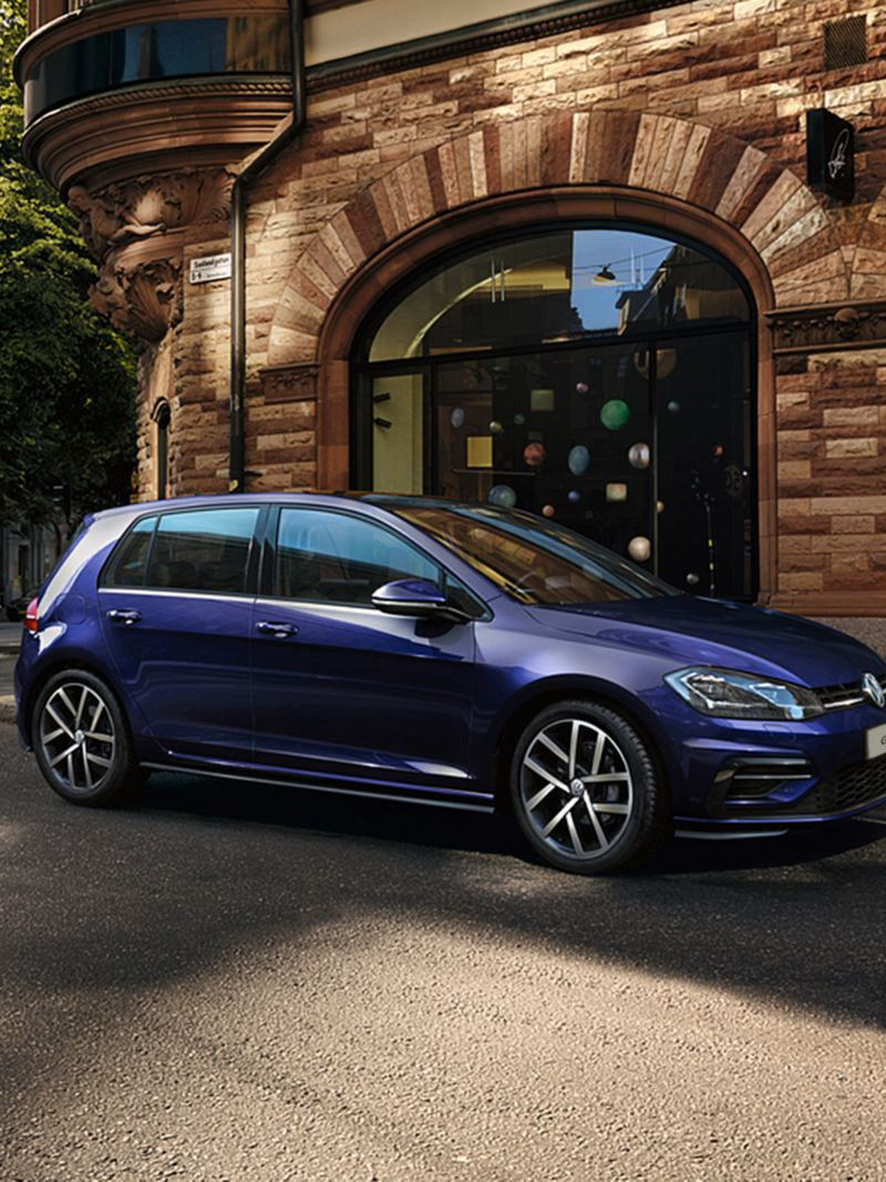 The Volkswagen Golf parked on a street - a man getting into the car