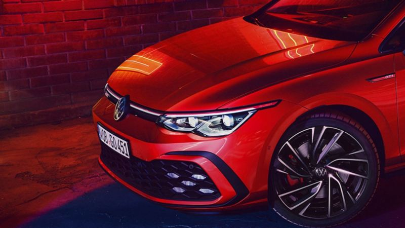 The driver's side headlight and bumper of a Golf GTI at night