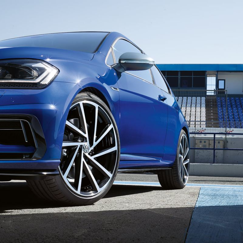 Close-up of the 18 inch Cadiz alloy wheel of the Volkswagen Golf R MK7 painted in Lapis Blue Metallic parked on a racetrack