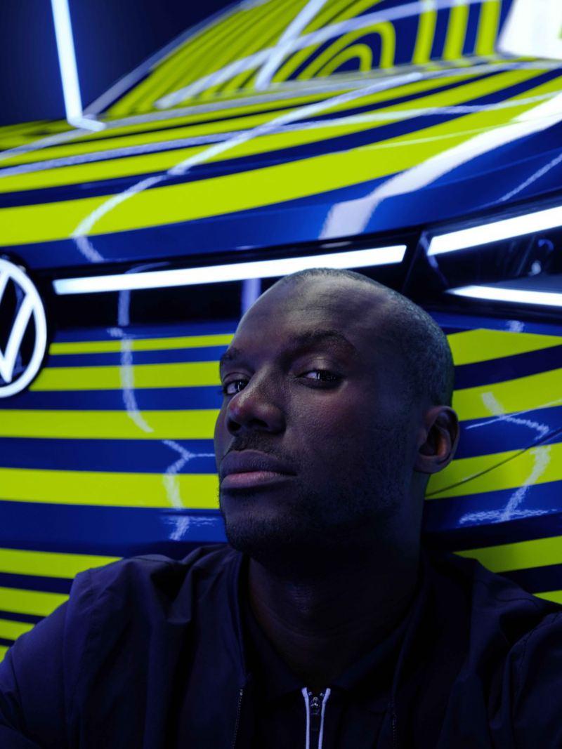 Homem encostado ao pára-choques dianteiro do Volkswagen ID.4