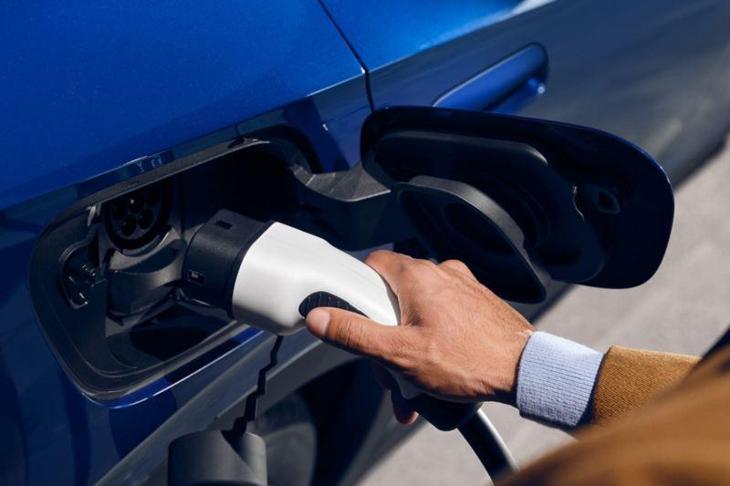 Un uomo mette in carica la sua Volkswagen ID.4 1 st tramite l'apposita presa di corrente.