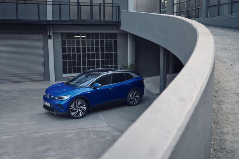 Vista laterale di Volkswagen ID.4 1st parcheggiata fuori da un edificio.