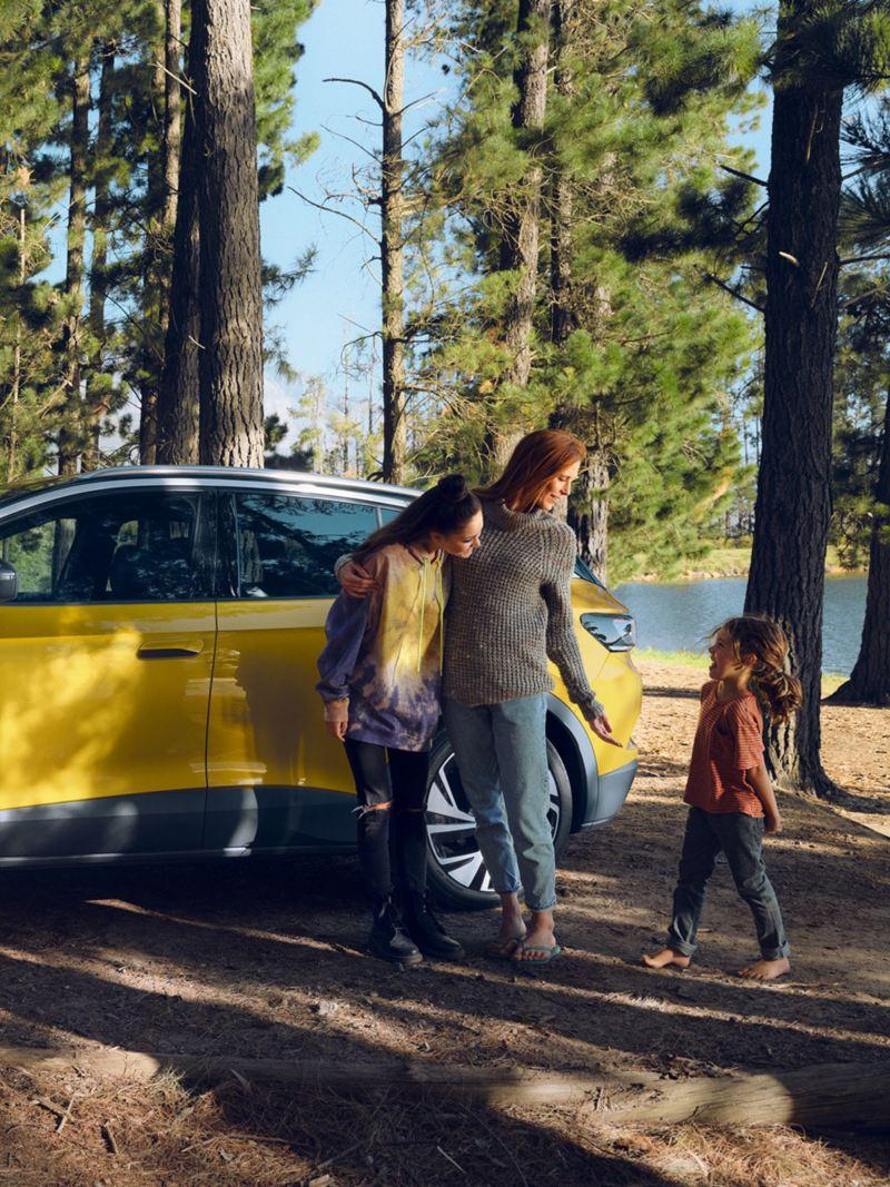 ID.4 från sidan, kvinna, två barn i skogen