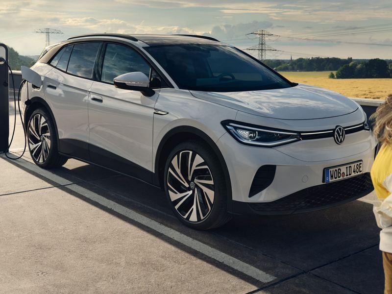 Le VW blanc ID.4 se trouve sur la place pour le chargement. Vue de côté et de face. Une fille passe en voiture.