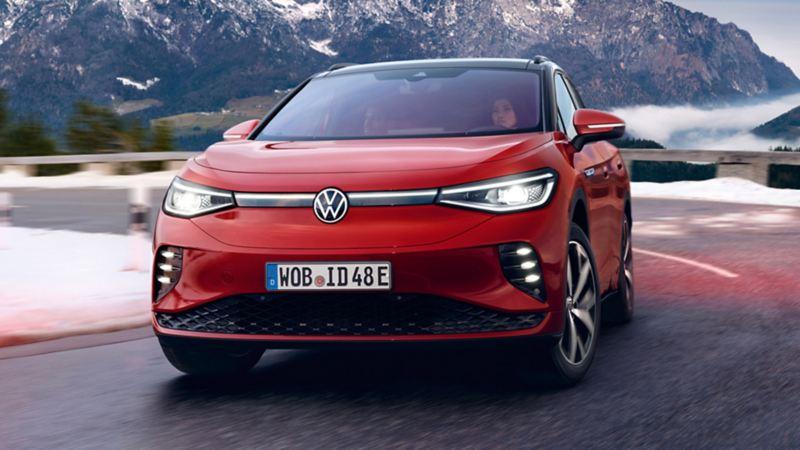 Sidan på en röd VW ID.4 GTX kör längs en väg omgiven av snötäckta berg
