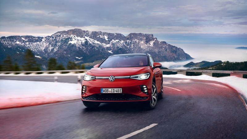 VW ID.4 GTX rouge, de face. Il roule sur une route sinueuse dans les montagnes couvertes de neige.