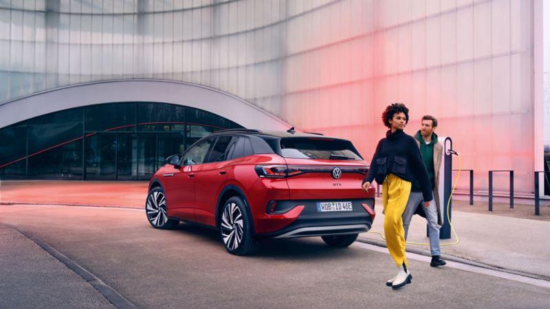 VW ID.4 GTX SUV sett bakfra parkert ved en ladestasjon, en kvinne og man går forbi