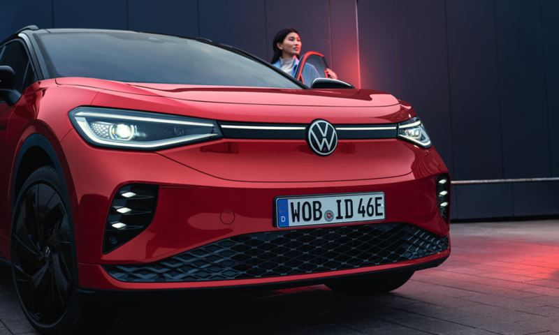 VW ID.4 GTX in rot steht auf Asphalt. Frau hat die Fahrertür geöffnet.