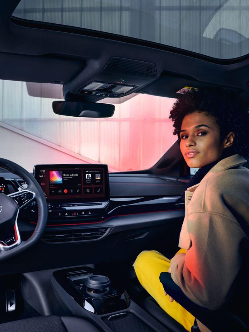 Wnętrze VW ID.4 GTX z widokiem na przednie siedzenia i kokpit. Kobieta siedząca na siedzeniu pasażera z widokiem do tyłu.