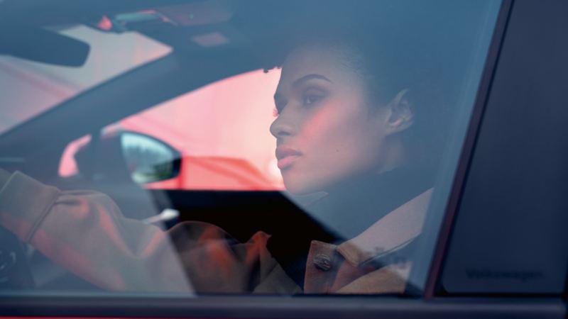 Kobieta siedząca w VW ID.4 GTX na fotelu kierowcy z ręką na kierownicy spoglądająca na zewnątrz.