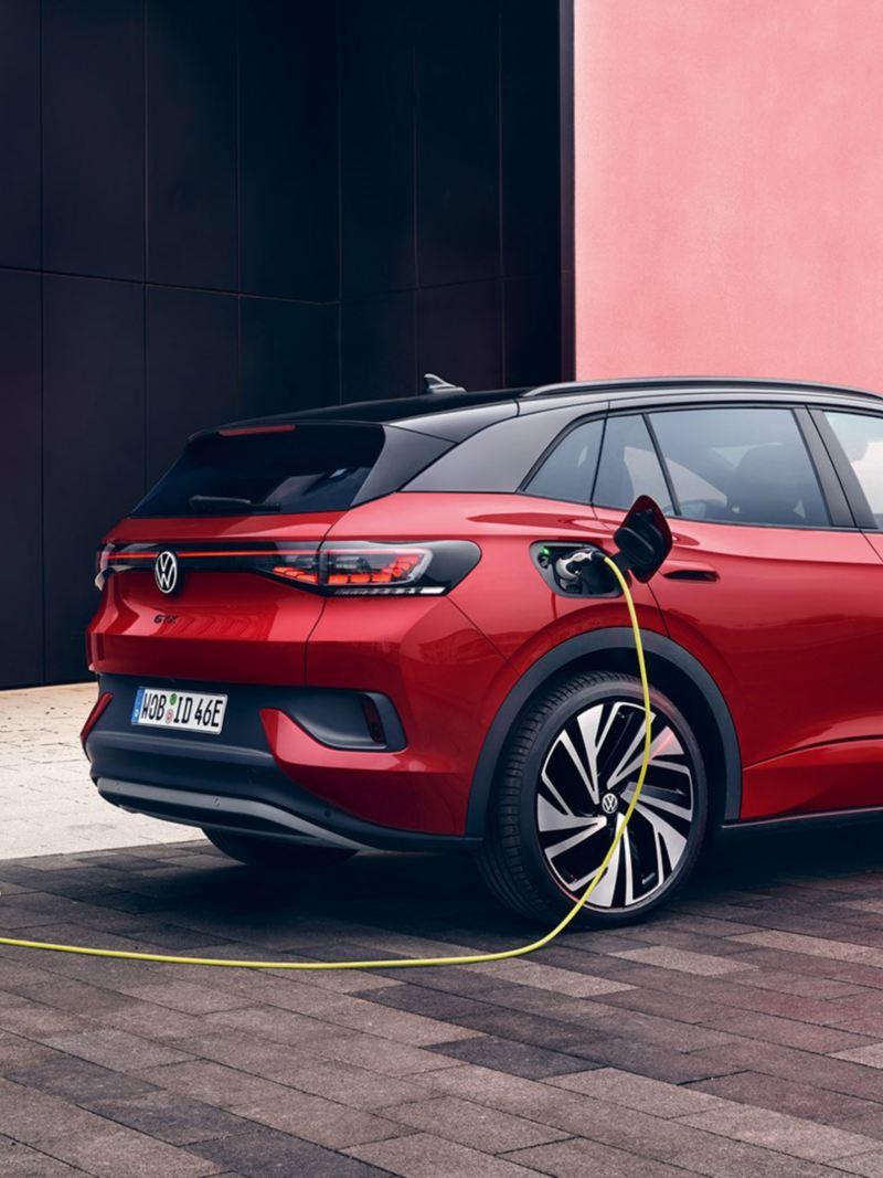 Sidvy av en röd VW ID.4 GTX som står på laddning. En kvinna är påväg mot elbilen.