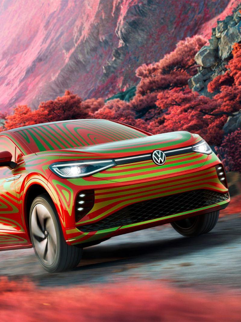 Vista 3/4 frontale dal basso di Volkswagen ID.5 GTX Camouflage su una strada in un paesaggio roccioso con arbusti rossi.