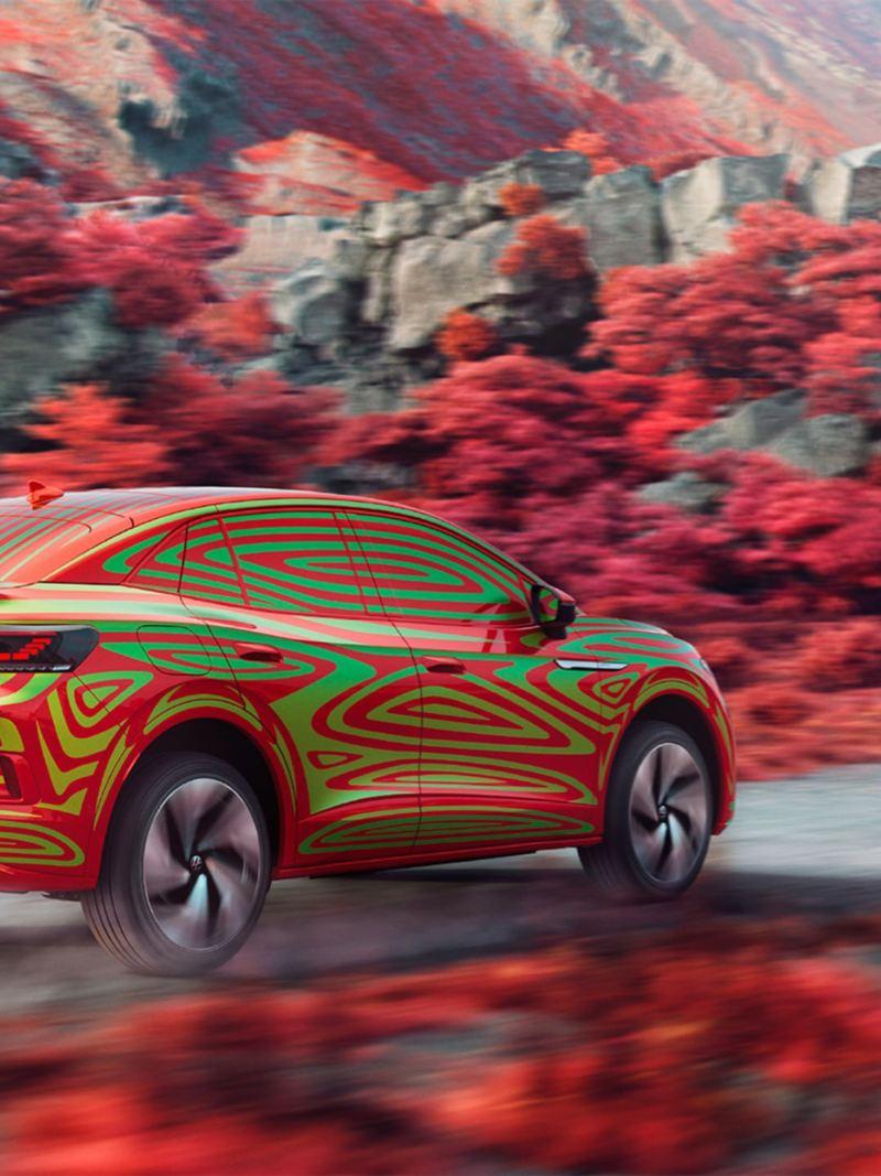 Vista laterale di Volkswagen ID.5 GTX Camouflage su una strada in un paesaggio roccioso con arbusti rossi.