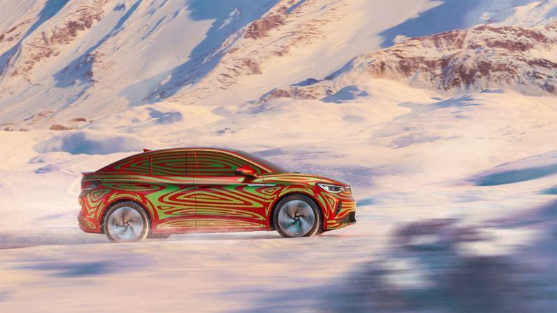 Vista laterale di Volkswagen ID.5 GTX Camouflage su una strada di montagna innevata.