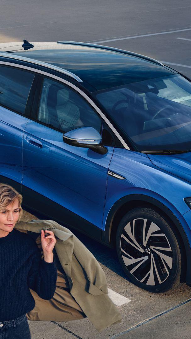 Una donna si allontana da una Volkswagen ID.4 vista 3/4 frontalmente, in carica presso una colonnina.