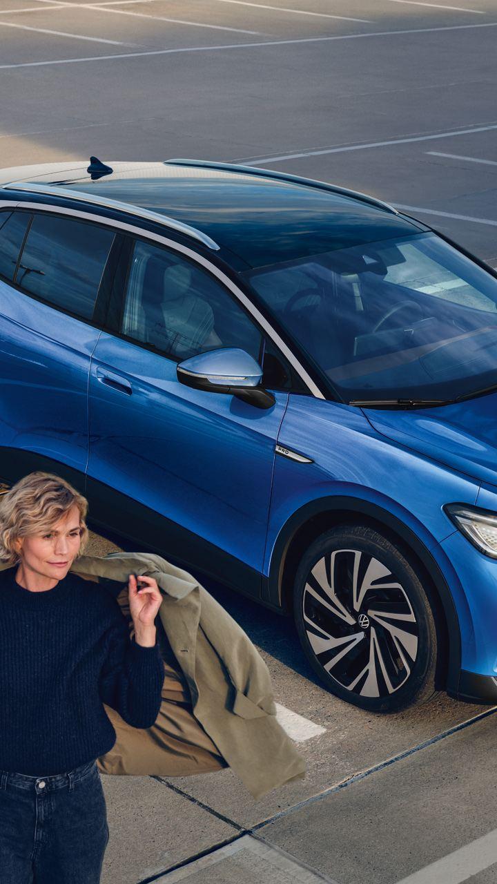 Una donna si allontana da una Volkswagen ID.4 1st, vista 3/4 frontalmente, in carica presso una colonnina in un parcheggio.
