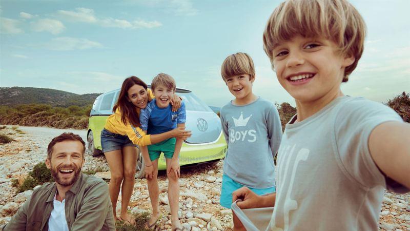 Una famiglia si scatta una fotografia davanti a Volkswagen ID. Buzz, parcheggiato su una strada sterrata e visto 3/4 frontalmente.