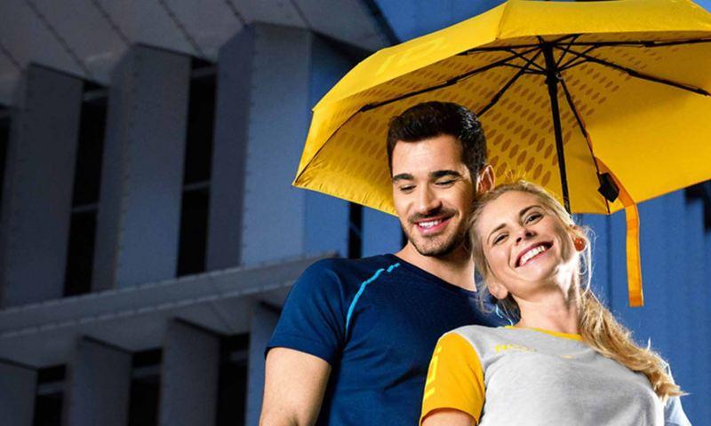 Un ragazzo e una ragazza sorridenti sotto un ombrello giallo originale Volkswagen.