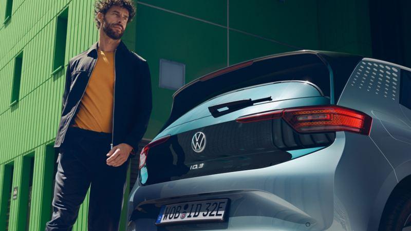Um homem aparece detrás de um carro elétrico Volkswagen ID.3
