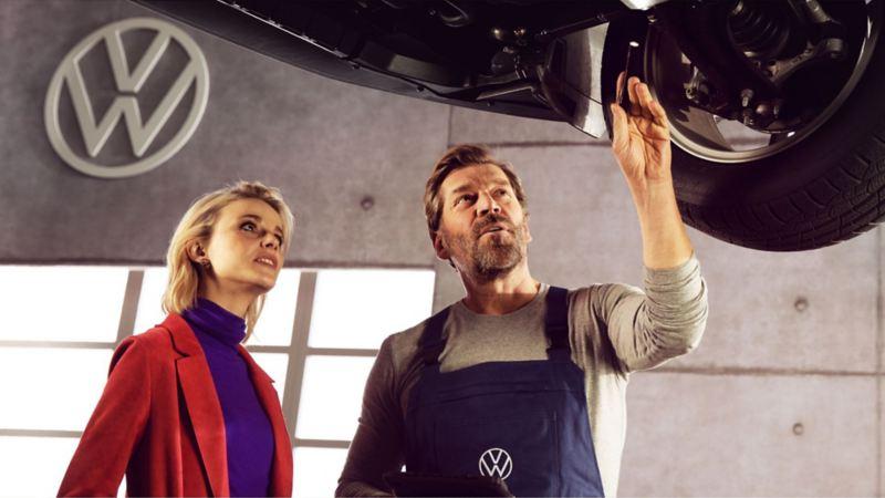 un homme et une femme regardent le dessous du véhicule pendant la réparation