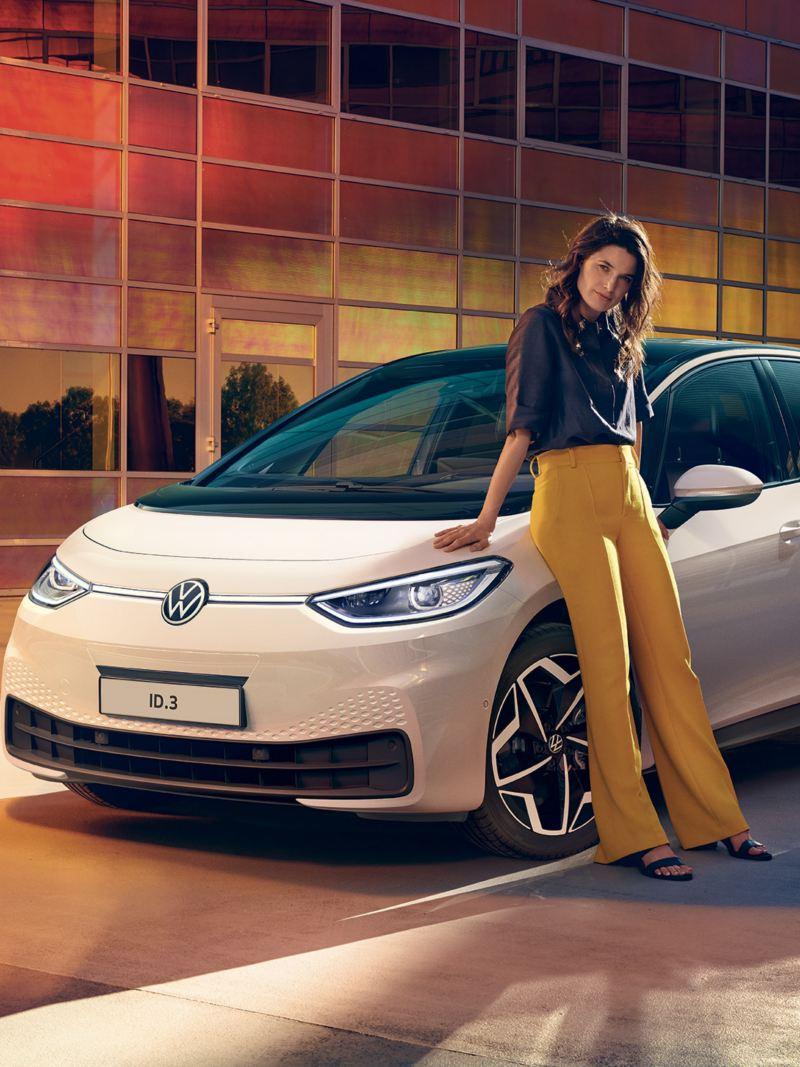 Una donna appoggiata a una Volkswagen ID.3 vista 3/4 frontalmente, parcheggiata davanti ad un edificio moderno.