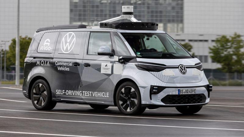 Vista 3/4 frontale del primo prototipo di Volkswagen ID.BUZZ AD per la guida autonoma, con carrozzeria camouflage.