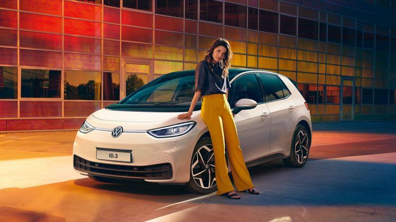 Ragazza appoggiata al cofano di Volkswagen ID.3.