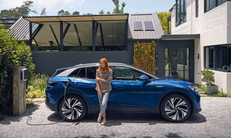 Nouveau ID.4 bleu en charge garée près de maison avec végétation et femme appuyée sur la voiture