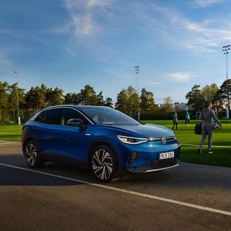 En blå ID.4 står parkerad vid en fotbollsplan, spelare i bakgrunden
